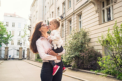 A mother holding her daughter and giving her a kiss in a street setting in Berlin. - p429m2182653 by Tamboly