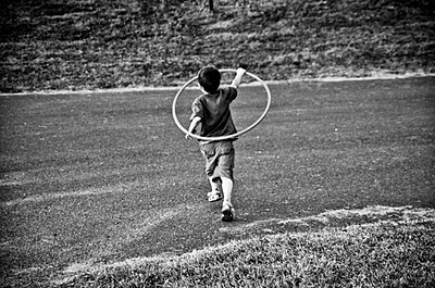 Young boy running with hula hoop, Otterburn Park, Quebec - p6071603 by Patrick LaRoque