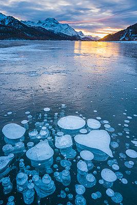 Silvaplana, Engadine valley, Switzerland. Frozen bubbles in the Lake Silvaplana (Silvaplanersee) on a winter sunset. - p651m2006928 by Marco Bottigelli