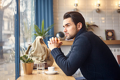 Side view of thoughtful man looking through window while sitting at cafe - p1166m1544059 by Cavan Images