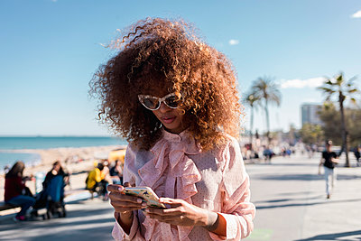 Stylish young woman using cell phone at seaside promenade - p300m2012879 by Mauro Grigollo