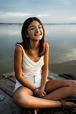 Girl with eyeglasses smiling while sitting on jetty against lake - p300m2241603 by Rafa Cortés