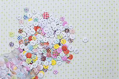 Directly above shot of multi colored various buttons on fabric - p301m1579634 by Alexandra C. Ribeiro