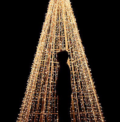 Silhouette of a young man in front of Christmas lights - p3741568 by Karin Smeds