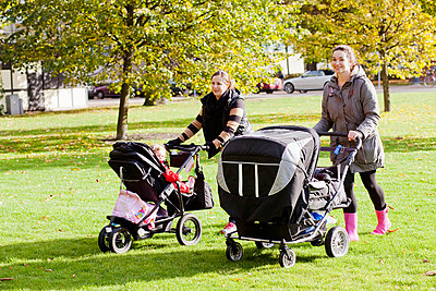 Happy female friends in warm clothing pushing baby carriages at park - p426m747445f by Astrakan
