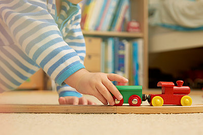 Baby boy playing with train set - p429m884741f by Emma Kim