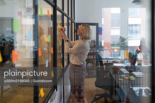 Mature businesswoman writing on adhesive notes on glass pane in office - p300m2156045 von Gustafsson