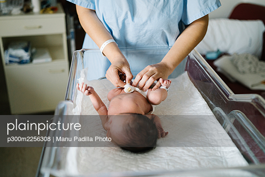 Mother wearing hospital gown changing newborn baby diaper while standing in hospital - p300m2256308 by Manu Padilla Photo