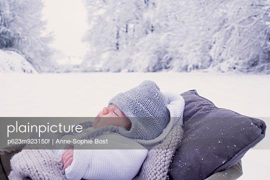Baby sleeping in bassinet in wintery scane - p623m923150f by Anne-Sophie Bost
