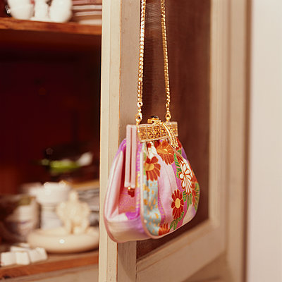 Small handbag hanging from cupboard - p1311m1136876 by Stefanie Lange