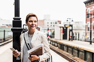 Mature woman using smart phone at commuter train station - p300m1191994 by Uwe Umstätter