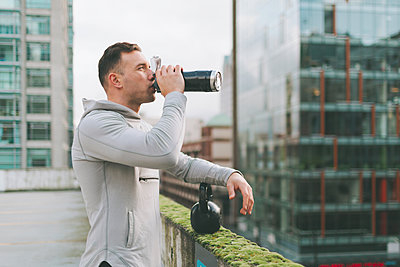 Man having a break from working out with a kettlebell in the city, Canada - p300m2169960 by Crystal Sing