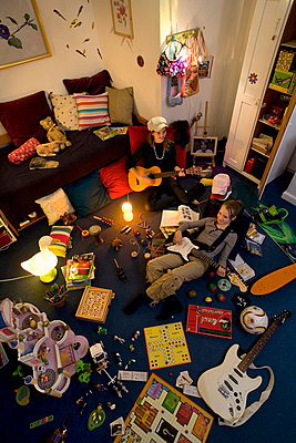 Two girls play guitar in crowded room - p4296237 by Lilian Henglein
