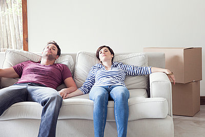 Couple relaxing on sofa while moving house - p623m958094f by Sigrid Olsson