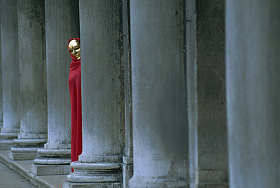Carnival model in red cape and gold mask peering from columns in St. Mark's Square, Venice, UNESCO World Heritage Site, Veneto, Italy, Europe - p8710394 by Lee Frost