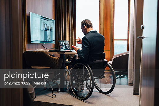 Disabled businessman with colleagues on video conference in office during pandemic - p426m2270622 by Maskot