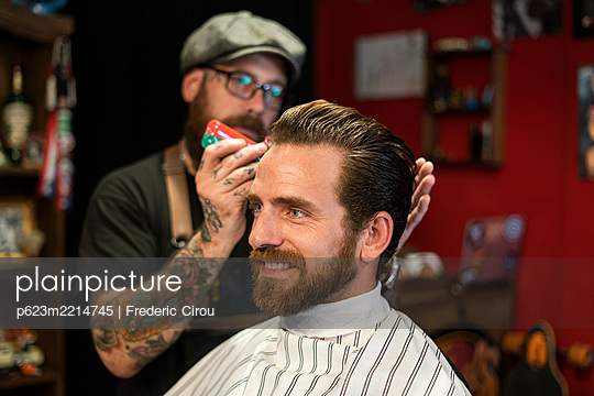 Hairdresser styling man's hair in salon - p623m2214745 by Frederic Cirou