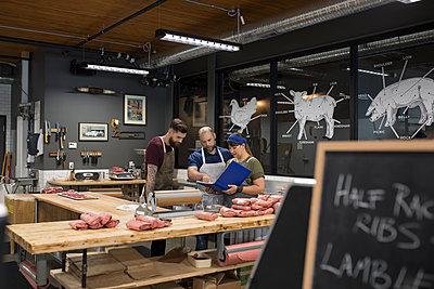 Butchers discussing paperwork in butcher - p1192m1493357 by Hero Images