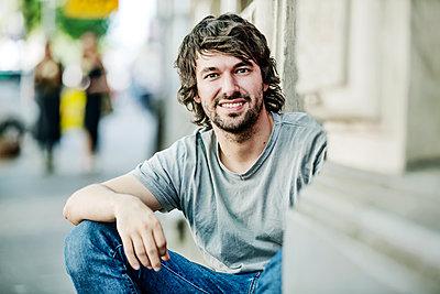 junger Mann sizt in der Stadt auf dem Bürgersteig in einem Hauseingang - p300m1550181 von Jan Tepass
