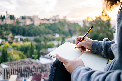 Close-up of man at observation point drawing a sketch of the Alhambra, Granada, Spain - p300m2188218 by Daniel González
