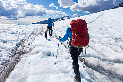 Couple and their dog backpacking on the Kennicott Glacier, Wrangell Mountains, Wrangell-St. Elias National Park, South-central Alaska; Alaska, United States of America - p442m2077667 by Amber Johnson