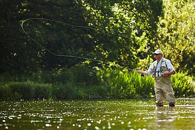 Senior man fly fishing at summer river - p1023m1192560 by Richard Johnson
