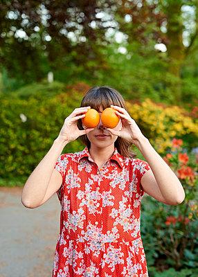 Frau hält sich Orangen vor die Augen - p1124m1134803 von Willing-Holtz
