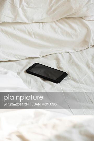 Smartphone auf dem Bett - p1423m2014734 von JUAN MOYANO