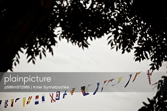 Blick auf eine Girlande mit vielen kleinen Nationalfahnen - p586m972989 von Kniel Synnatzschke