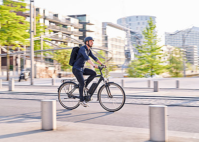 Bicycle courier riding an electric bike - p1124m2052997 by Willing-Holtz