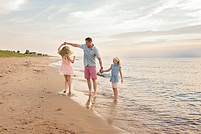 Father playing with daughters on shore at beach - p1166m1568989 by Cavan Images