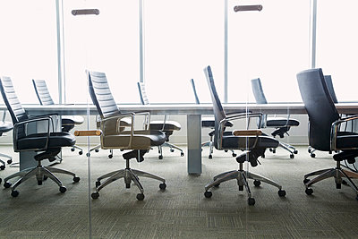 Chairs around empty conference room table - p1192m1016640f by Hero Images