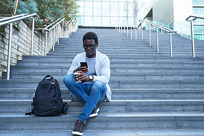 Entrepreneur using mobile phone while holding disposable cup on staircase at financial district - p300m2241023 von Pete Muller