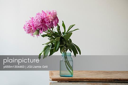 Pink flowers in jar on table