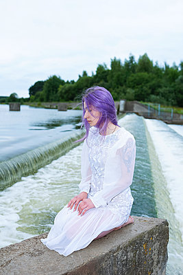 woman sitting on her knees near a waterfall - p1166m2136598 by Cavan Images