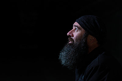 Side portrait of a smiling bearded man with a black background a - p1166m2136924 by Cavan Images