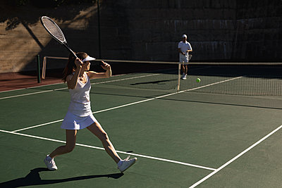 Woman and man playing tennis on a sunny day - p1315m2131516 by Wavebreak