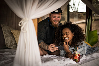 Happy couple on bed in a lodge with smartphone and fresh ice tea - p300m2170647 by Malte Jäger