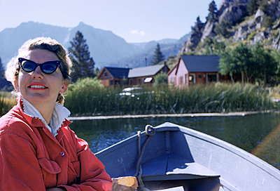 Caucasian woman sitting in boat on lake - p555m1444185 by PBNJ Productions