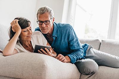 Reifes Paar entspannt mit Tablet auf dem Sofa - p586m1178503 von Kniel Synnatzschke