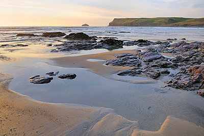 Tide retreating at sunset leaving tide pools among rocks, with Pentire Head in the background, Polzeath, Cornwall, England, United Kingdom, Europe - p871m807638 by Nick Upton