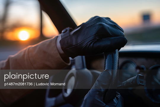 Hand on the wheel at sunset - p1487m2081736 by Ludovic Mornand