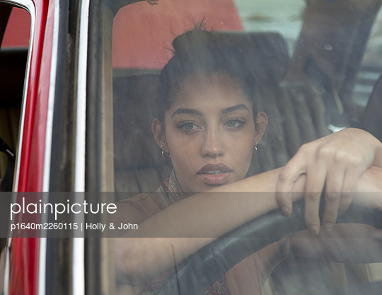 Teenage girl at the steering wheel in a car - p1640m2260115 by Holly & John