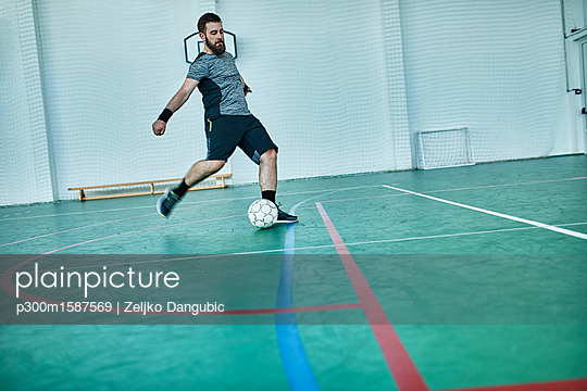 Man playing indoor soccer shooting the ball - p300m1587569 von Zeljko Dangubic