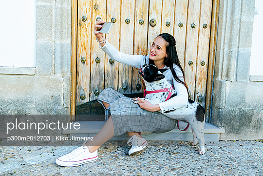 Young woman using smartphone, taking a selfie with her dog - p300m2012703 von Kiko Jimenez