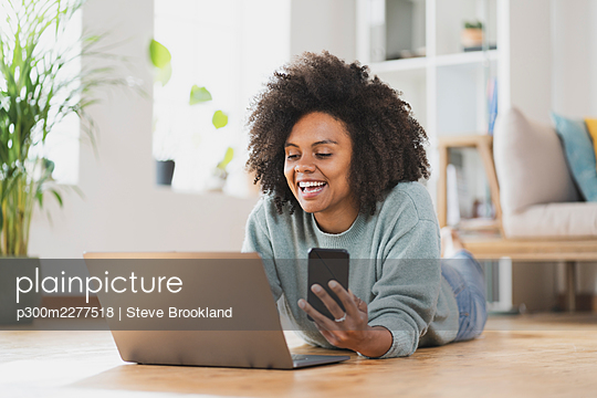 Smiling woman with mobile phone using laptop while lying on floor at home - p300m2277518 by Steve Brookland