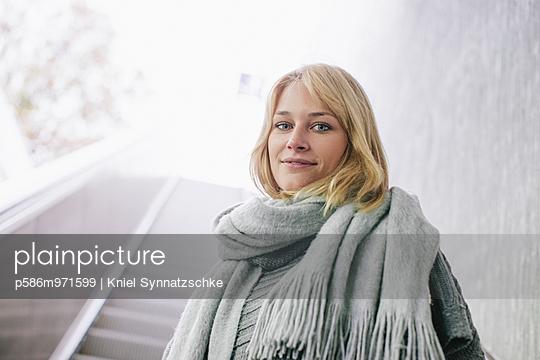 Junge Frau mit Schal auf einer Rolltreppe - p586m971599 von Kniel Synnatzschke