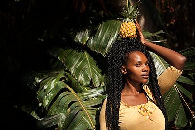 schöne Afrikanerin trägt Ananas auf Kopf - p045m1465146 von Jasmin Sander
