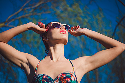 young woman looking at sun with sunglasses - p1150m2288748 by Elise Ortiou Campion