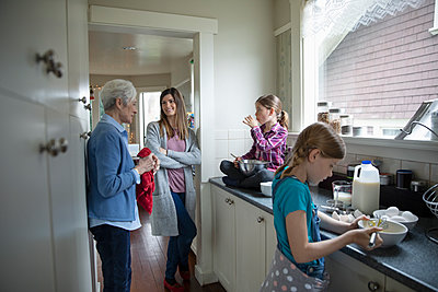 Multi-generation women baking in kitchen - p1192m1583428 by Hero Images